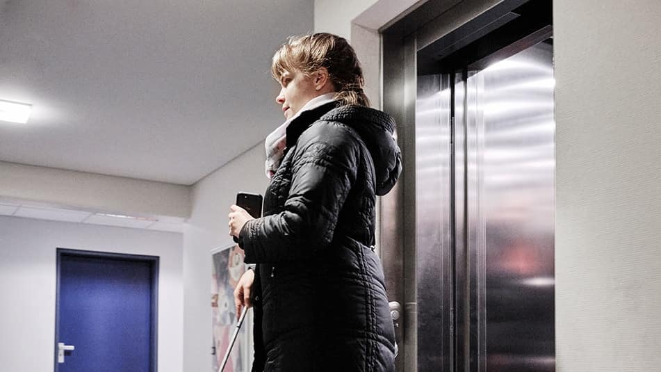 A woman who is blind exiting an elevator using the Blindsquare application on her mobile phone and her white cane.